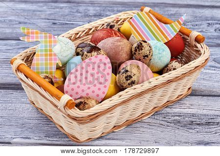 Easter basket with paper cutouts. Pile of eggs. Invite family for Easter picnic.