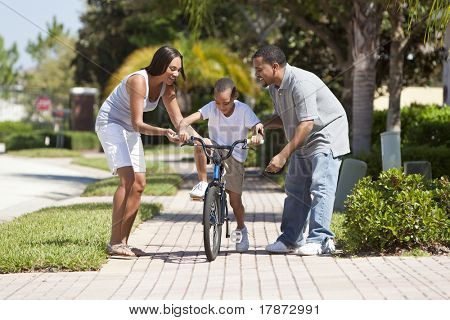 A young African American family with boy child riding his bicycle and his happy excited parents encouraging him.