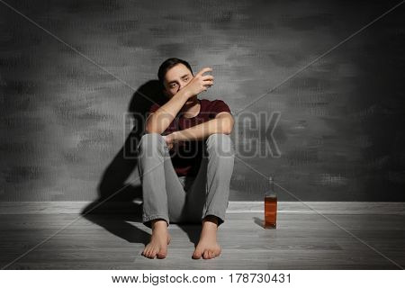 Handsome depressed man sitting on floor at home