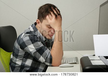 Handsome depressed man working on computer