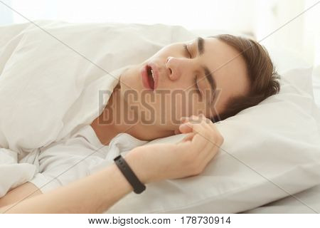 Young man with sleep tracker resting in bed at home