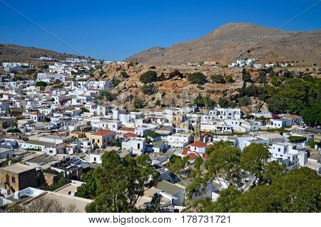View of the town of Lindos white houses under the hill and the blue sky on the island of Rhodes in Greece