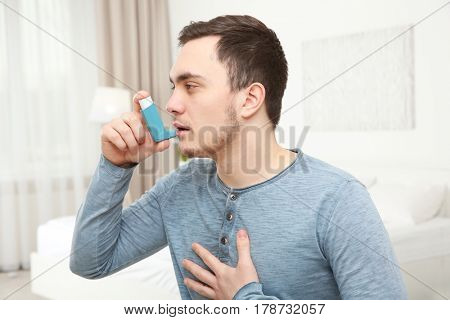 Young man using inhaler during asthmatic attack at home