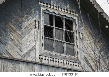 Wooden old house window with broken glass.