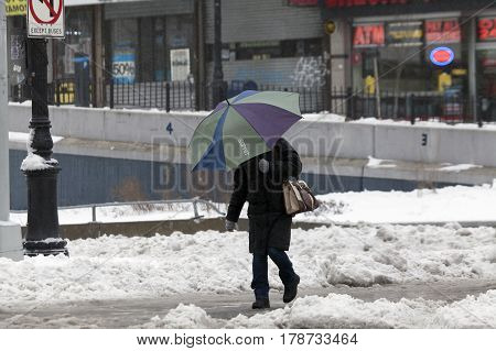 BRONX NEW YORK - MARCH 14: Person using an umbrella during snow storm. Taken March 14 2017 in New York.