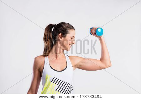 Attractive young fitness woman in white singlet, working out with dumbbell. Slim waist, perfect fit female body. Studio shot on gray background.