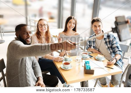 Lets take pictures. Young handsome mulatto guy is taking picture with his friends by using selfie stick during common meeting at cafe.