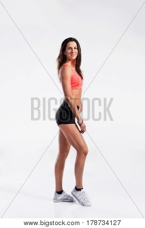 Attractive young fitness woman in orange sports bra and black shorts. Slim waist, perfect fit female body. Studio shot on gray background.