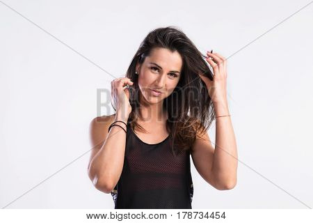 Attractive young fitness woman in black tank top playing with hair. Studio shot on gray background.