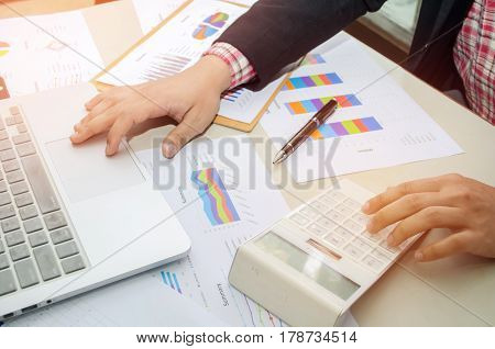 businessman hand working with business document and laptop computer notebook on wooden desk as concept with business and working concept, selective focus and vintage tone, color tone effect