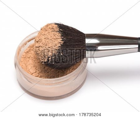 Closeup of make up brush with jar of loose cosmetic powder on white background. Shallow depth of field, focus on powdery brush bristle