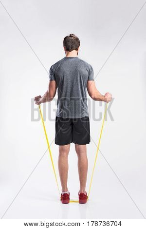 Handsome hipster fitness man in gray t-shirt working out with rubber band. Studio shot on gray background. Rear view.