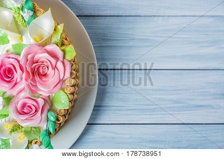 Delicious cake with roses lily and leaves on light blue wooden table with free space for your text.
