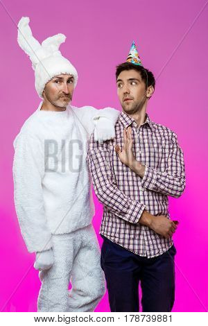 Drunk man and rabbit at birthday party over purple background. Copy space.