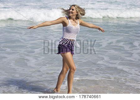 Caucasian blonde female having fun in the sun dancing around along the seashore in Bohemian clothing