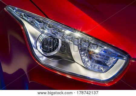 Car headlight with led and xenon lamps of modern sport car with red bodywork