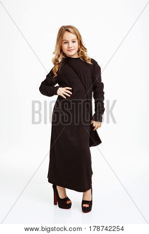 Nice blonde girl in black maxi dress posing with hand on hips, looking straight.