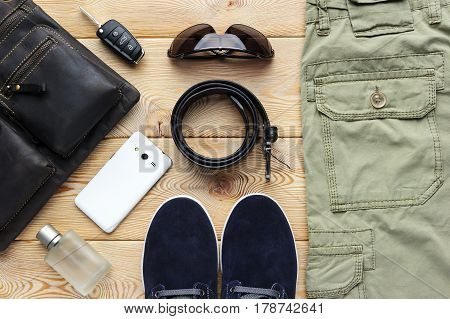 Young man accessories for spring or summer season in casual style, jeans, shoes, belt, eyeglasses, bag, mobile phone, car key and perfume on brushed wood background, fashion industry