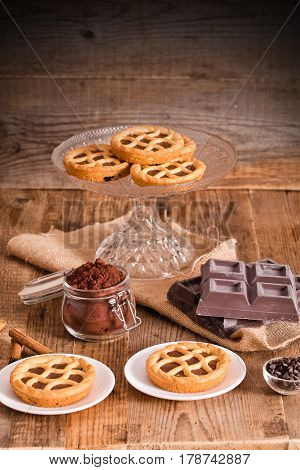 Chocolate tarts and chocolate block on wooden table.
