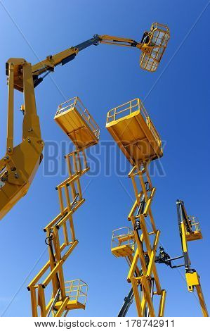Scissor lift platform, cherry picker, aerial platform with bucket, articulating boom and other yellow construction cranes and machines, heavy industry, blue sky on background, bottom view