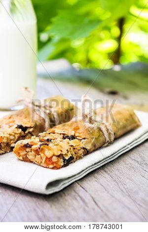 Homemade granola bars with oat flakes, raisin, dried apricot, dried plum with a bottle of fresh milk, selective focus