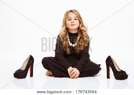 Beautiful girl with big curls sitting on floor next to black heels shoes. White background.