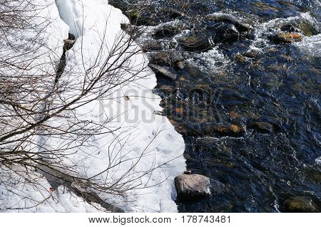 The Falschauer river in the Ulten Valley in South Tyrol with melting snow on the embankment and bubbling water.