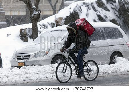 BRONX NEW YORK - MARCH 14: Man makes delivery on bike in snow storm. Taken March 14 2017 in New York.