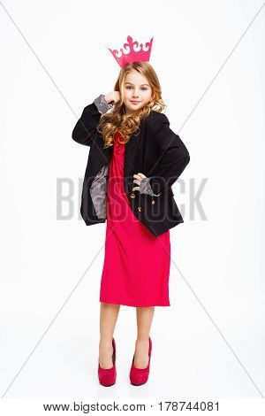 Girl with right hand on head, left hand on hip, posing in mother's clothig.