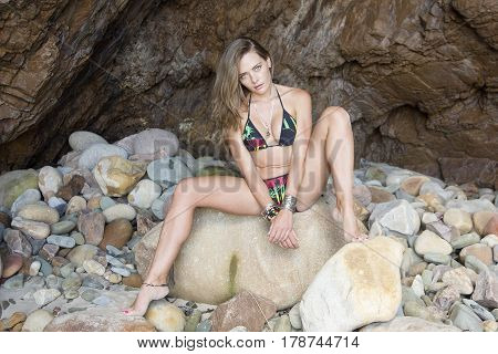 A caucasian model poses on a rock on a stoney beach with a large slab of stone in the background