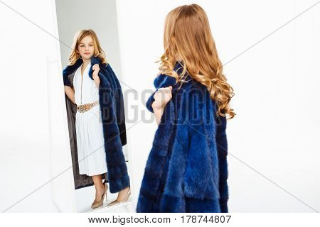 Beautiful girl with curls posing in fake fur coat, stylish dress, mother's shoes, admiring image.