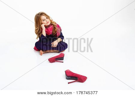 Girl sitting on floor shoeless. Kid in elegant clothing looking straight with charming smile.