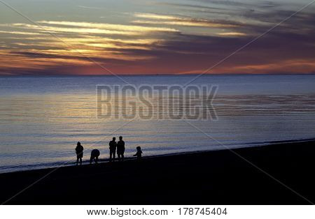Wide view of a beautiful red/orange sunset with clouds over the blues of the North Atlantic highlights a family in silhouette at the shoreline of Race Point Beach, Provincetown, Cape Cod, Massachusetts as the last light of sunset falls in mid September.