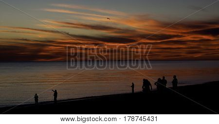 A brilliant red sunset with clouds over the North Atlantic highlights many people in silhouette along the shoreline of Race Point Beach, Provincetown, Cape Cod, Massachusetts as the last light of sunset falls in mid September.