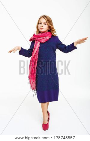 Full length shot of blonde girl parodying model walk, posing in mother's dress. White background