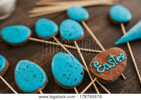 Easter blue cake pops on the wood rustic table for easter celebration, closeup.
