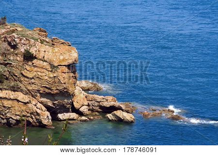 Wild rocks rise from sea. Marine landscape with views of the skyline and mountains. Panorama of the boundless water space is the craving for travel.