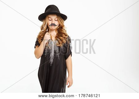 Adorable little girl with beautiful curls holding moustache mask on a stick. Close up.