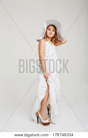 Beautiful girl in romantic summer outfit. Posing with hand on head. Looking straight. White background.