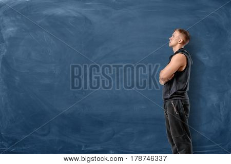 Muscular young man is standing his arms crossed and looking up on blue chalkboard background. Sport and healthy lifestyle. Keep fit. Athletic body