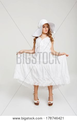 Nice girl in romantic summer look holds white skirt out. Isolated on white background.