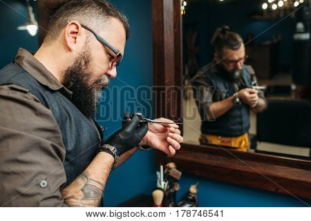 Barber check scissors sharpness before work day. Bearded hairdresser prepare instruments and workplace for haircut, reflection in mirror, free space