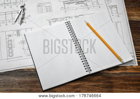 Open blueprints on wooden table background with a pencil. Engineering and design. Construction projects. Planning.
