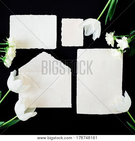 Paper envelop with white card and tulip flowers. Flat lay, top view, isolated on background