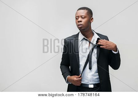 Afroamerican office employee. Tough work, hard breathing, problems, pressing staff, inability to rest. Grey background with free space.