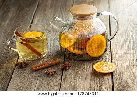 Glass teapot and cup of hot green tea with slices of tangerine, cinnamon and star anise on a wooden table