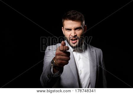 Displeased young successful businessman in suit ponting finger to camera over black background. Copy space.
