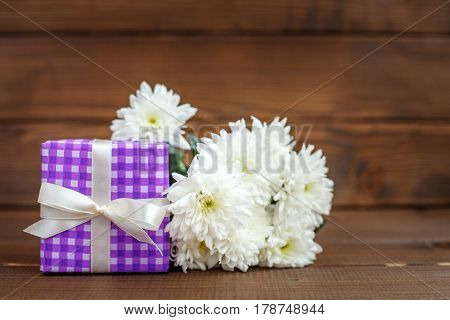 Gift and white flowers. The concept of Mother's Day birthday March 8.