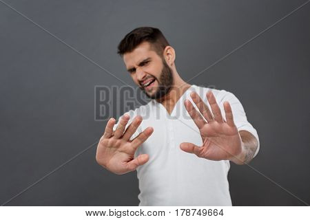 Displeased young handsome man refusing, stretching hands to camera over grey background. Copy space.