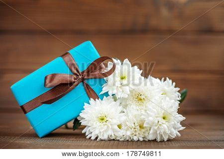 Wooden background with a gift and flowers chrysanthemums. The concept of Mother's Day birthday March 8.